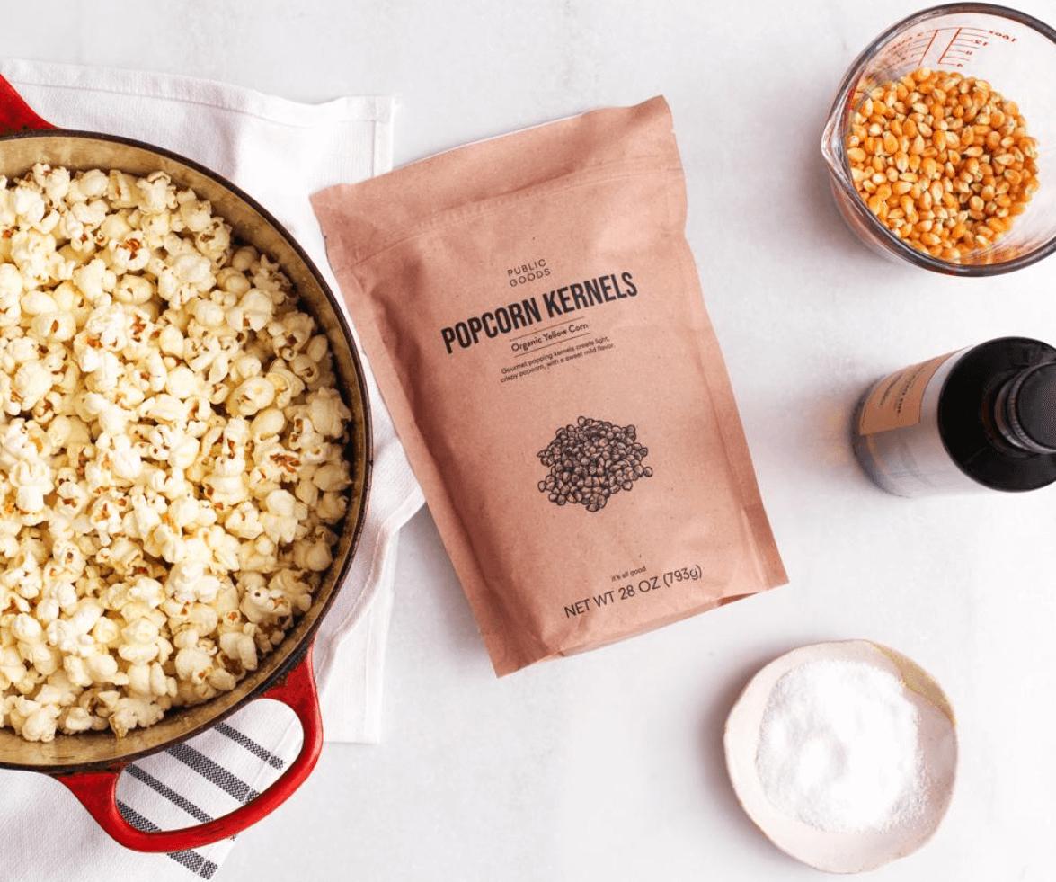 popcorn in red pot, bag of popcorn kernels, popcorn kernels in measuring cup, bottle of olive oil, salt