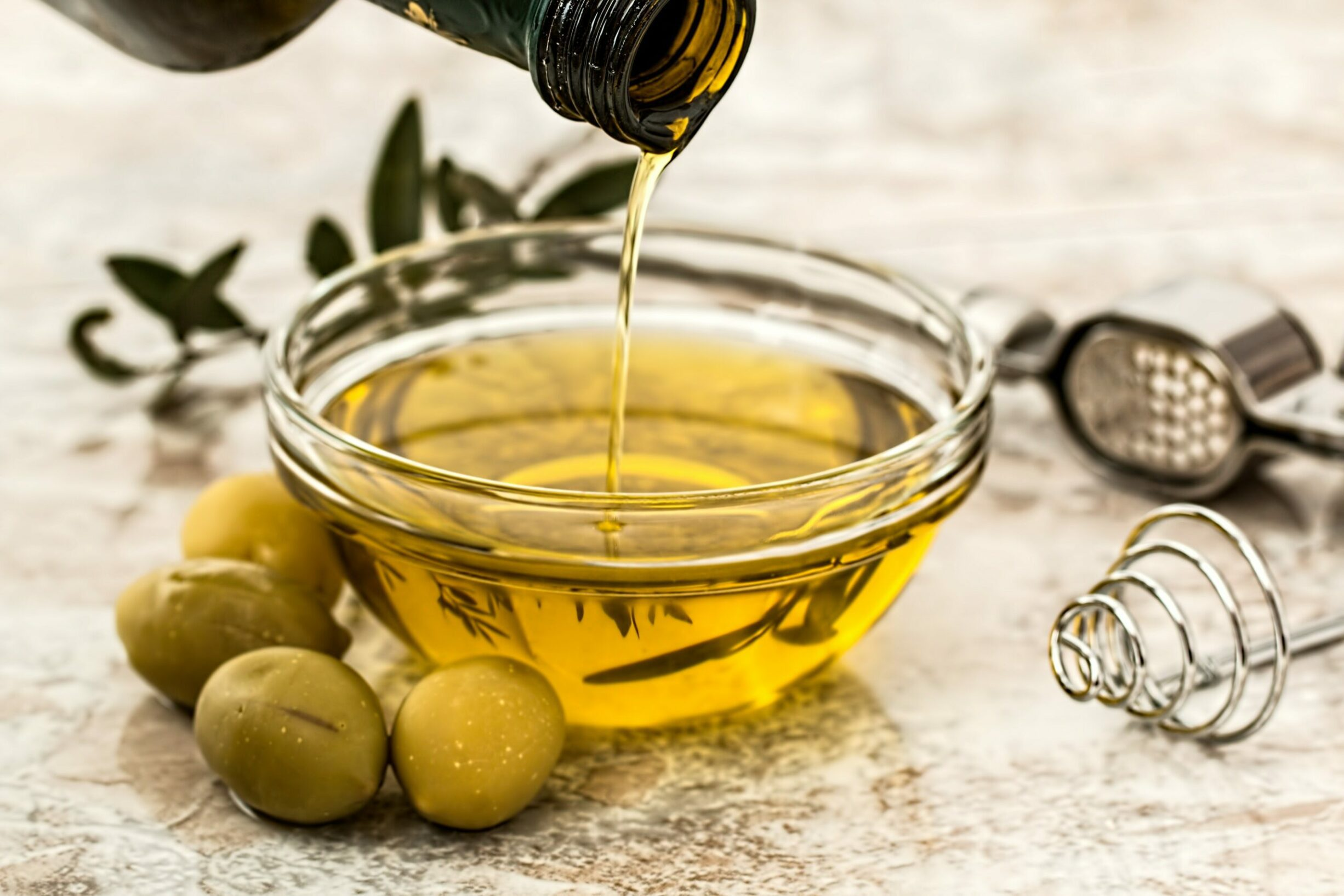Image of olive oil being poured in a clear bowl with olives and olive leaves around it