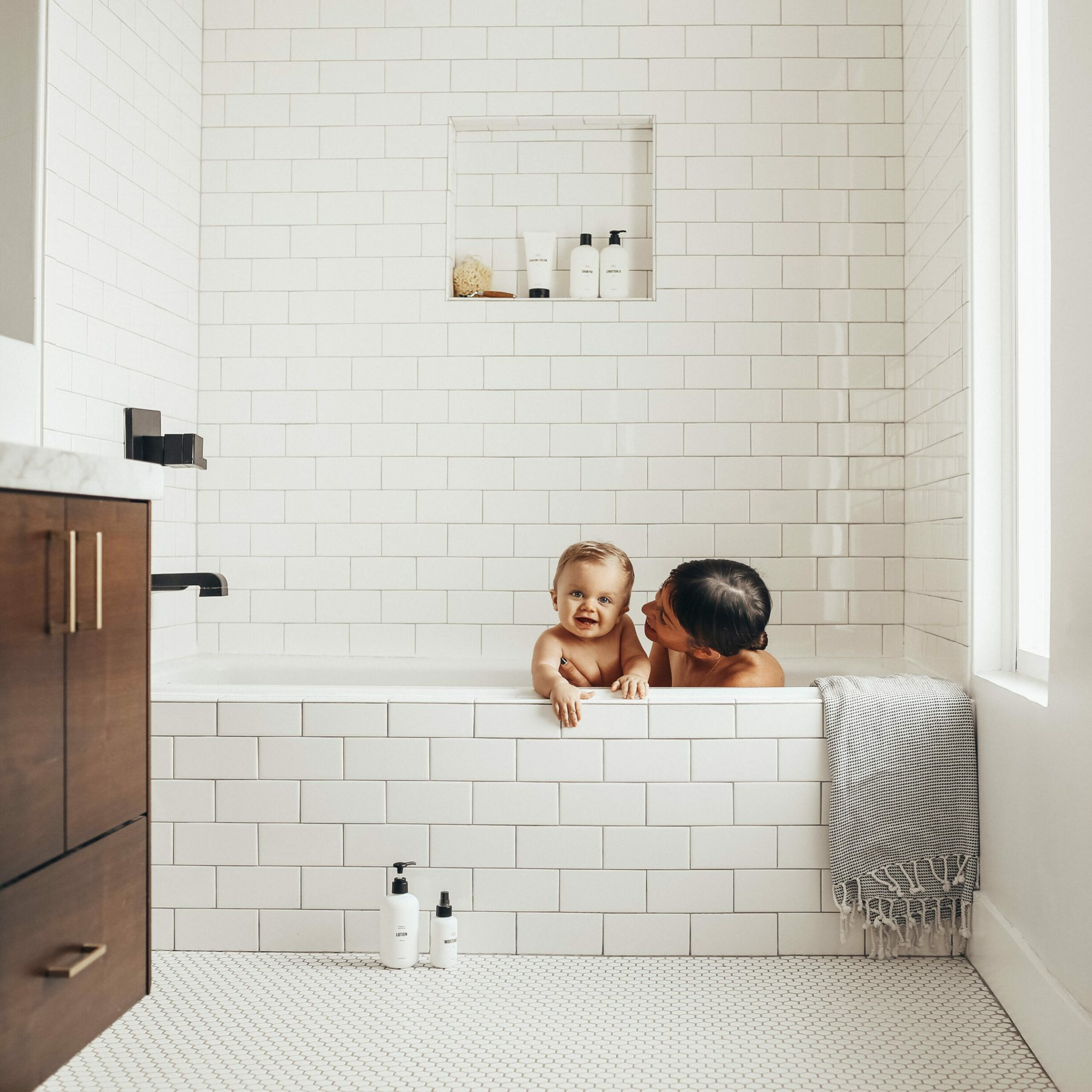 mother and child inside a bath tub using public goods products
